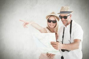 Happy tourist couple using map and pointing against white background